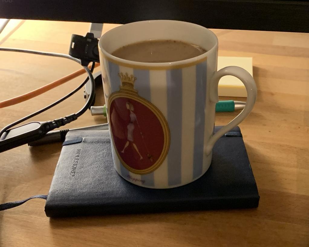 A mug using a Moleskine notebook as a coaster